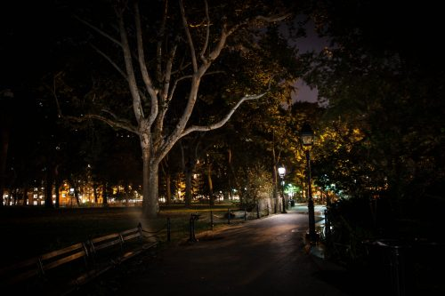 Washington Square Park at night, with a ribbon of the city visible in the distance, the park is dark, and as you will find out haunted!