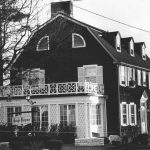 photo is black and white and shows the amityville horror house in 1973 from the side.