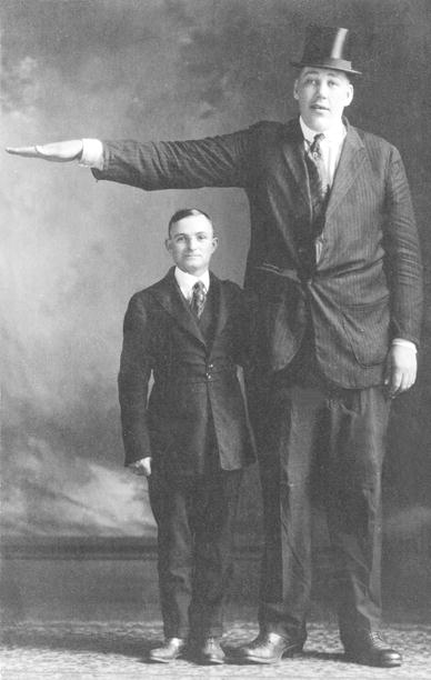 photo shows a man with gigantism standing next to a man without the disorder. A huge height difference is seen.