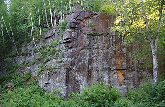 photo shows a large rock quarry wall