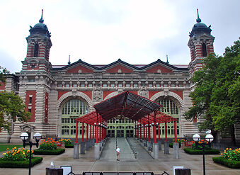 photo shows the entrance to the ellis island museum, with tan brick and red trim.
