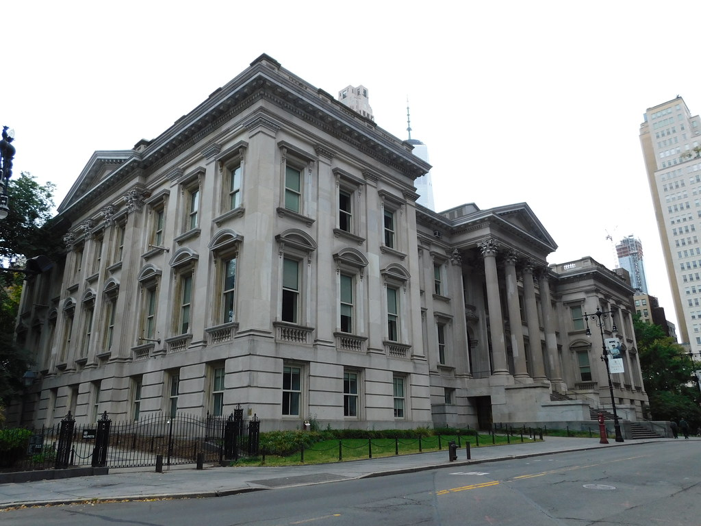 Photo shows the outside front of the Tweed Courthouse. The pillars of the main entrance are also shown and taller skyscrapers stand in the background. The entirety of the building is tan cement.