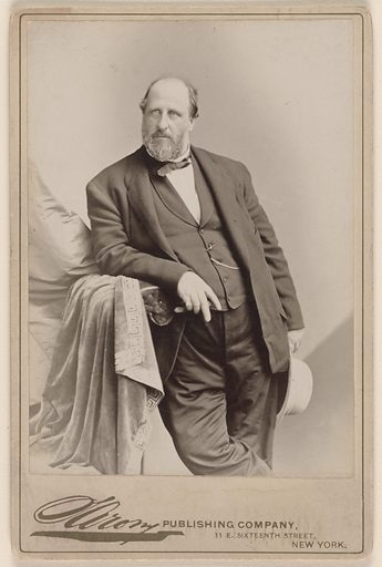 Photo shows William Tweed in an expensive suit. He is holding his hat and leaning against a chair.